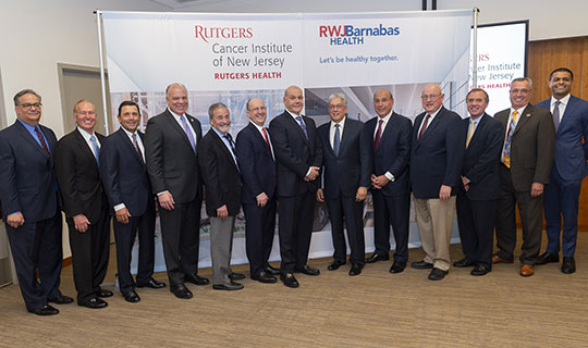 Members from RWJBarnabas Health, Rutgers Health, and the Mayor of New Brunswick, James T. Cahill in front of the rendering of the new CINJ Cancer Pavilion