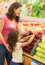 Mother and child picking an apple at the grocery store