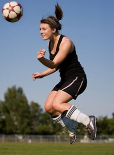 Girl heading the ball in soccer