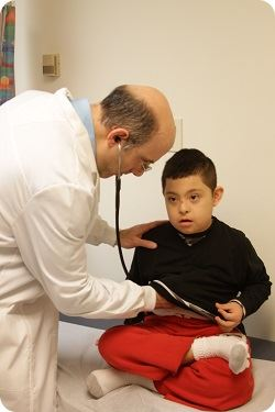 doctor checking heart of young boy