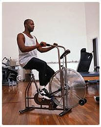 Man working out on fan cycle bike