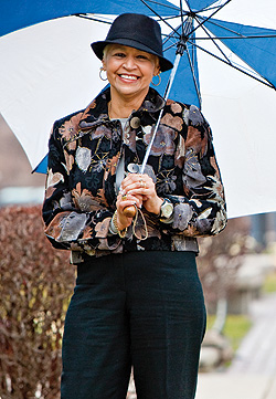 smiling woman in hat holding umbrella