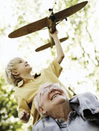 Child sitting on grandfather's shoulders while playing with a toy plane