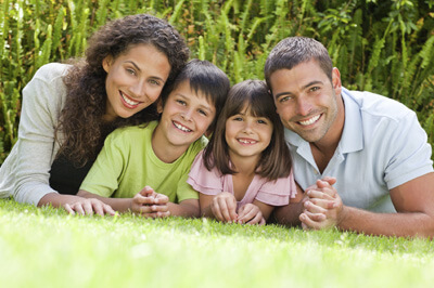family of four on grass smiling