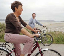 old couple riding bikes along the beach