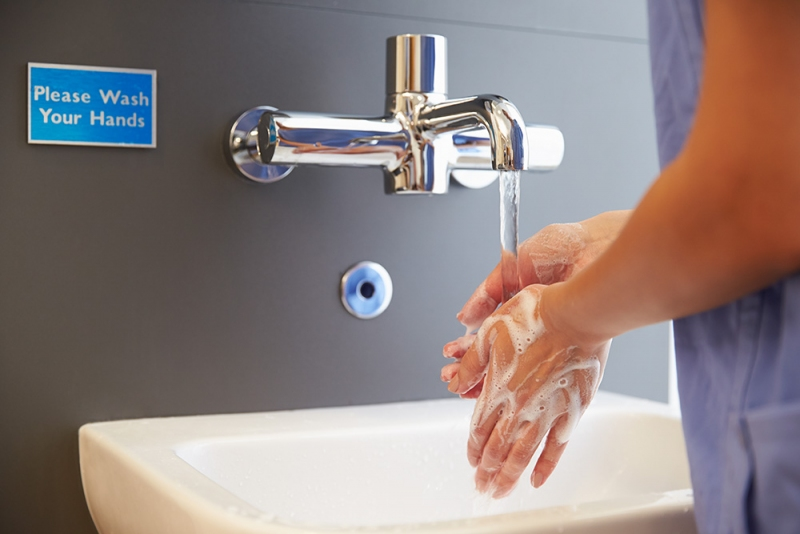 Physician washing hands in sink